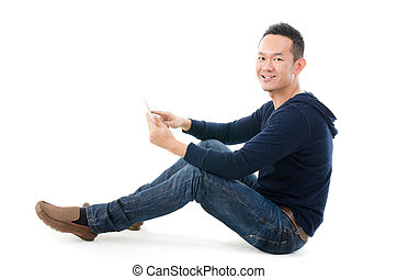 Asian man holding tablet computer isolated on white background.