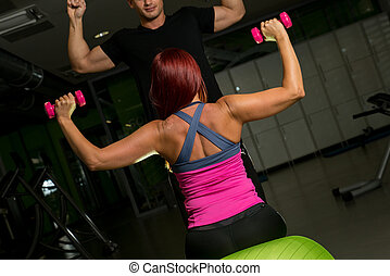 Woman and Personal Trainer in gym with dumbbells - Woman...