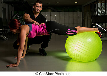 Woman exercising in gym with personal trainer