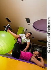 Instructor Assisting Woman In Doing Sit-Ups At Gym -...