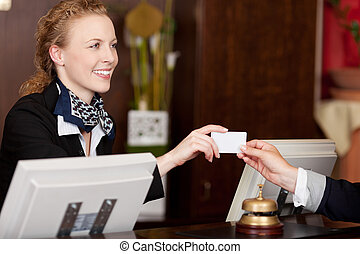 Smiling receptionist handing over a card - Smiling stylish...
