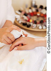 Beautician applying hand cream during a manicure in a salon...