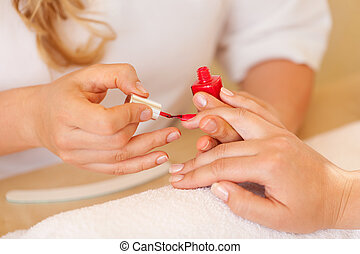 Beautician applying nail varnish in the salon while busy...