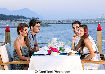 Couples celebrating at a seaside restaurant - Two attractive...