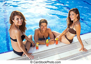 Happy man between two women at the swimming pool