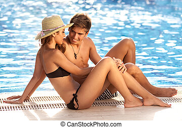 Attractive couple at the edge of a pool