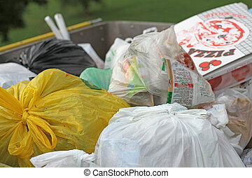trash into a dumpster full of garbage and solid waste - bags...