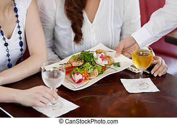 Waiter serving a plate of salad to a woman guest in a...