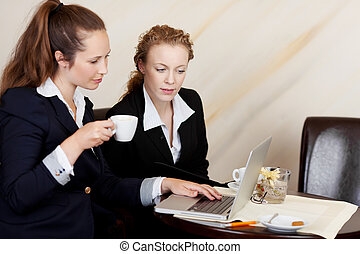 Two employees looking at the screen of a laptop