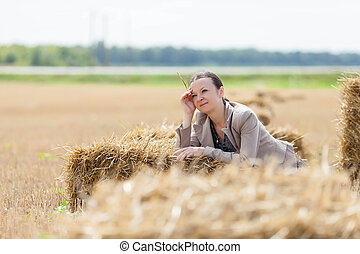girl relaxes on a haystack