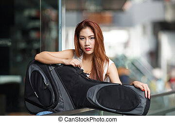 Young beautiful woman posing outdoor with her guitar gig...