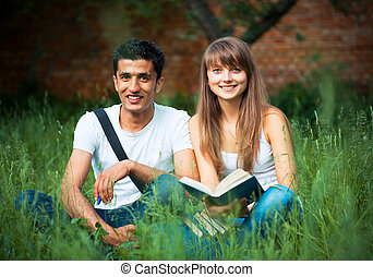 Two students guy and girl studying in park on grass with...