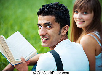 Two students guy and girl studying in park on grass