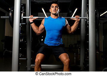 Fitness Trainer doing squats with barbells - Fitness Trainer...