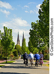 Cycling to the church - Group of men cycling on a spring day