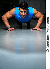 Healthy young guy doing push up exercise - Portrait of a...
