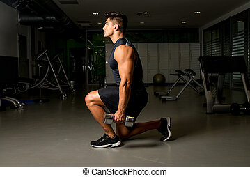 Gym Workout with Dumbbell Lunge - Young Man Exercising...
