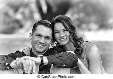 Black and White version of a happy young couple sitting on...