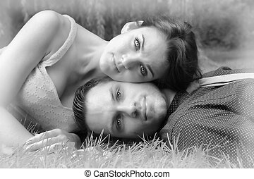 Black and white version of a young couple laying on the grass with the woman's head resting on the man in a garden setting