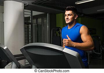 Exercising on a treadmill - Man running on treadmill, focus...