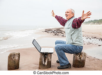 Old man with notebook on beach - Happy old man with a laptop...