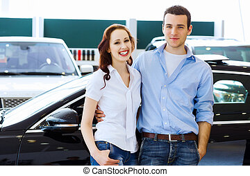 Young happy couple at car salon - Two pretty young people...