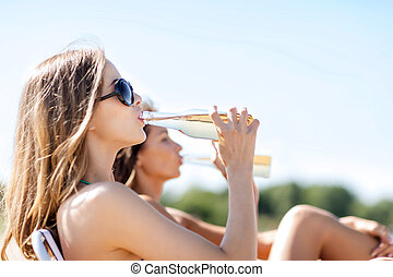 girls with drinks on the beach chairs - summer holidays and...