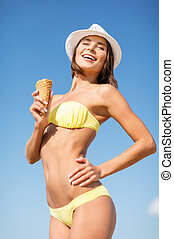 girl in bikini eating ice cream on the beach - summer...