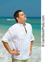 Handsome man enjoy vacation on a beach, with blue sea on...