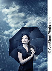 optimism - woman stands under a umbrella and is waiting for...