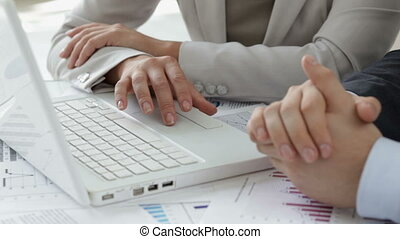 Laptop users - Close-up of business people using a laptop in...