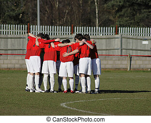 Team spirit - A soccer team having a group hug before...