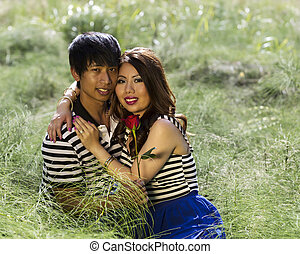 Young Adult Holding Each Other while sitting in Grass Field