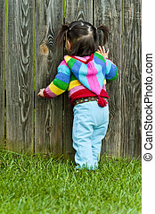 Baby toddler peeping through fence hole - Baby toddler girl...