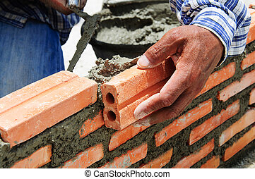 construction mason worker bricklayer installing brick with...