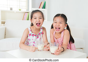 Children drinking milk. Asian family at home. Beautiful...