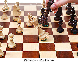 black king throws white king in chess game - hand with black...