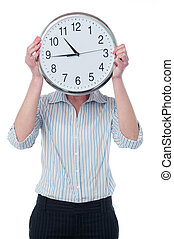 Woman hiding her face behind wall clock