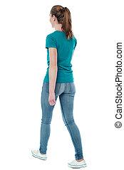 Young woman walking, studio shot - Casual woman walking away...