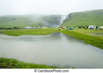 tent camp near Skogarfoss waterfall in Iceland, rainy summer...