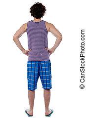 Rear view of a man in beach wear - Man in beach wear facing...