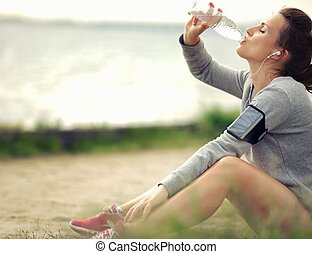 Female Runner Drinking Water - Female runner sitting on the...