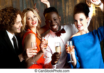 Couples enjoying champagne or wine at a party - Group of...