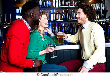 Group of three friends in a bar drinking beer - Friends...
