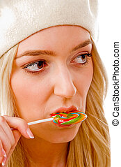 portrait of smiling female licking candy on an isolated...