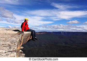 Sitting on Top of the World - hiker rests and admires views of Blue Mountains on a beautiful sunny day.  Selective focus.