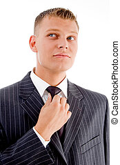 businessman adjusting his tie on an isolated white...