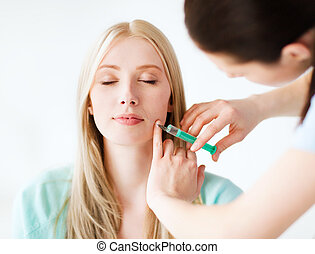 beautician with patient doing botox injection - healthcare,...