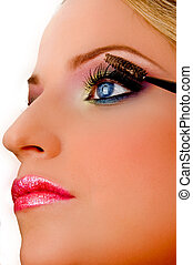 close view of model putting eyeliner on an isolated white...