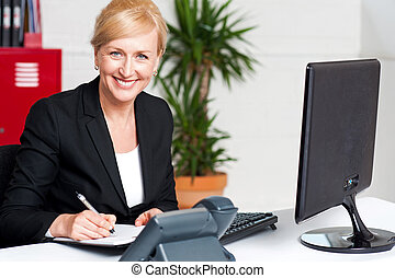 Business executive writing her appointments - Smiling...